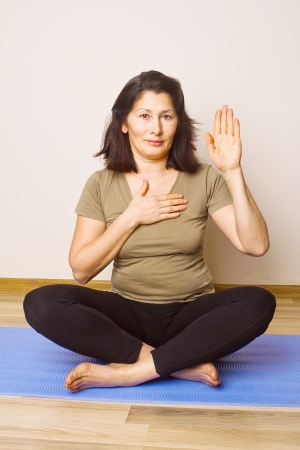 Asian woman on an mat out into a yoga position   photo
