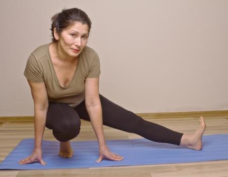 Asian woman on an mat out into a yoga position