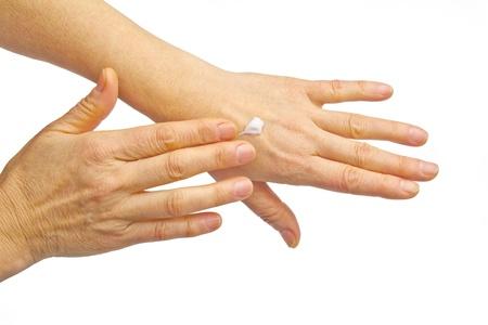 Female hands applying hand cream isolated on white background