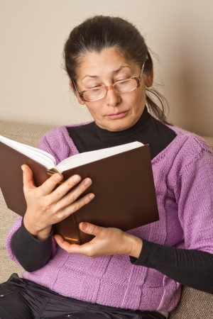 Asian woman reading a book at home.