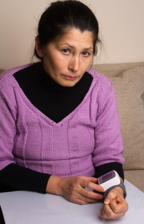 Woman with a home measuring her blood pressure Stock Photo - 17975354
