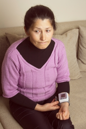 Woman with a home measuring her blood pressure Stock Photo - 17975419