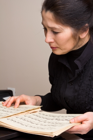 Asian woman looking at musical papers Stock Photo