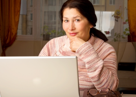 Senior woman with laptop, relaxing on the couch