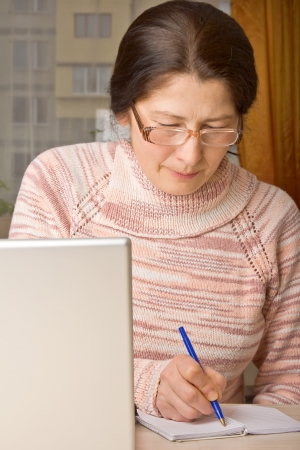 Senior woman with laptop, relaxing on the couch  photo