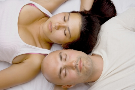 Vertical image of a couple lying head to head Stock Photo