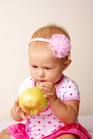 Baby girl eating a green apple photo
