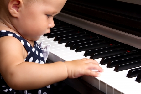 Beautiful baby girl plays piano