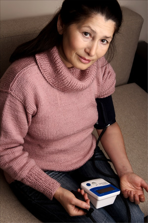 Woman with a home measuring her blood pressure