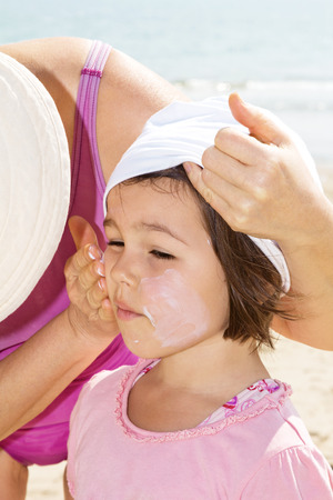 Mother applying sunblock on her daughter Stock Photo