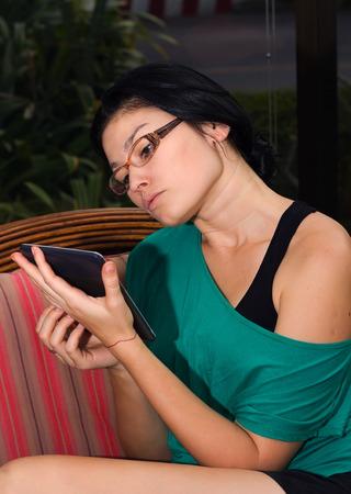 Beautiful young woman reading e-book