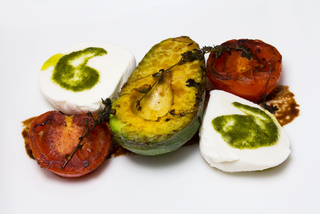 Grilled avocados, tomatoes and feta cheese and garnished with sauce Stock Photo