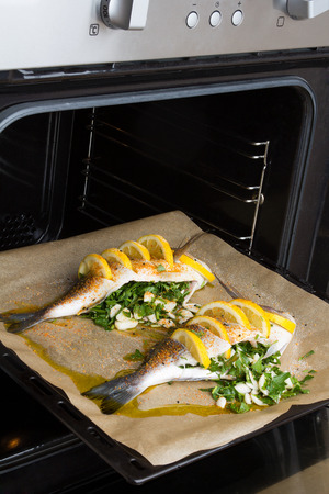 Cook fish sea bream fish with lemon, parsley,garlic