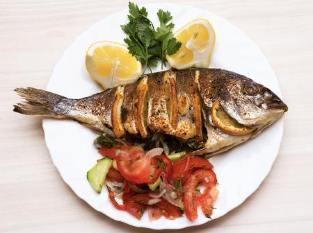 Gekookte vis zeebrasem vis met citroen, peterselie, knoflook