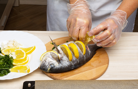 Cooked fish sea bream fish with lemon, parsley,garlic  photo