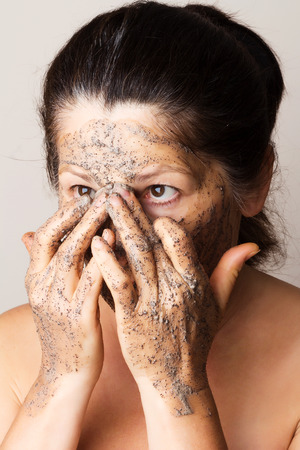 Mature woman making cosmetic mask from coffee, sour cream. photo