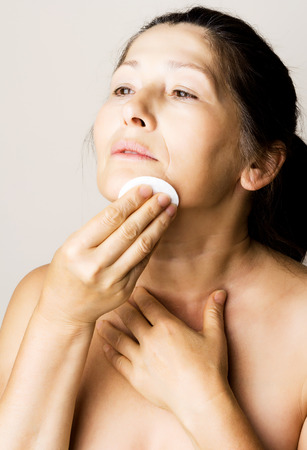 beautiful mature woman: Asian woman clean face with lotion and cotton pad