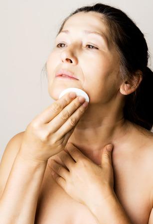 mujer maquillandose: Cara limpia Mujer asi�tica con loci�n y almohadilla de algod�n