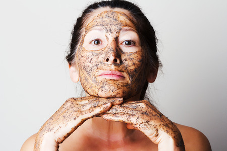 masked woman: Mature woman making cosmetic mask from coffee, sour cream.