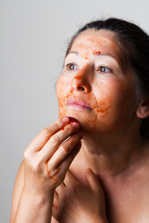 Mature woman making cosmetic mask from strawberry. photo