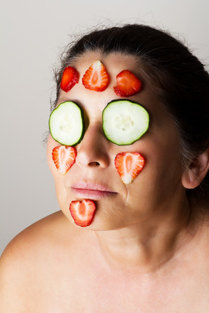 Mature woman making cosmetic mask from cucumber. photo