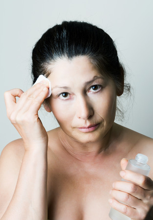 Asian woman clean face with lotion and cotton pad photo