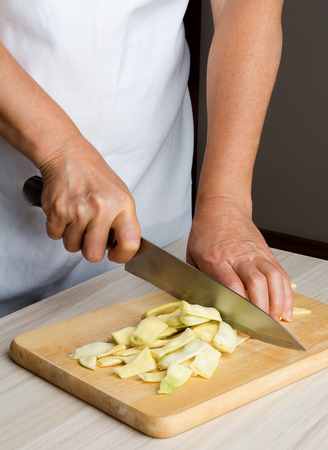 Womans hand slicing a yellow beans photo