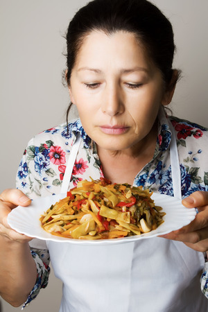 Female chef shows dish of yellow beans and vegetables.