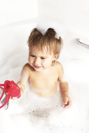 suds: Little girl surrounded soap suds.