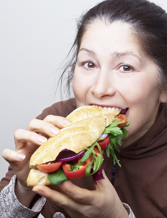 Woman with a sandwich with tomatoes, bell pepper,red onion and arugula. Stock Photo