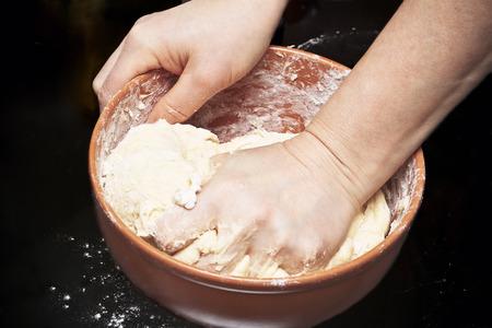 Woman kneading bread dough in kitchen