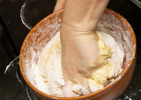 kneading: Woman kneading bread dough in kitchen