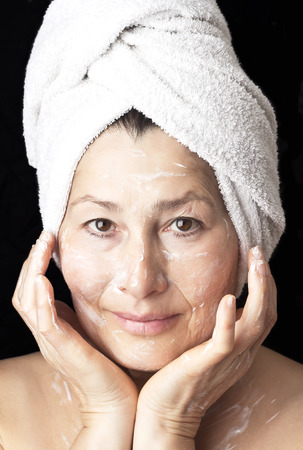 Beautiful older woman makes a mask Stock Photo