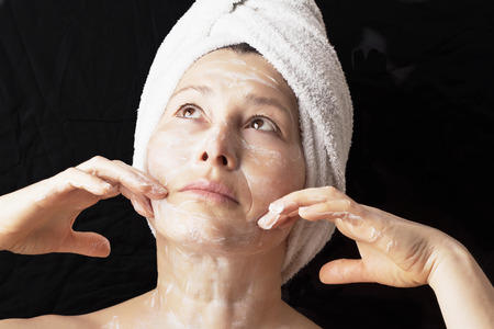 aging woman: Beautiful older woman makes a mask Stock Photo