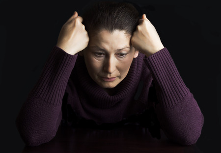 female face closeup: Mature woman in deep sitting thought at home.