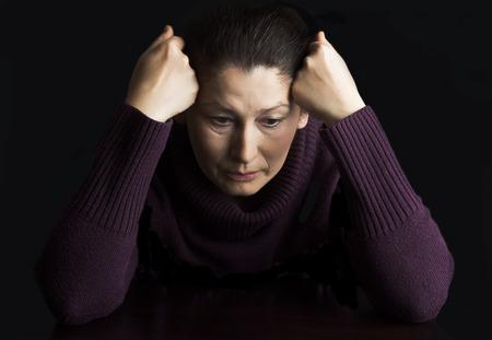 cara triste: Mujer madura en lo profundo de estar pensado en casa.
