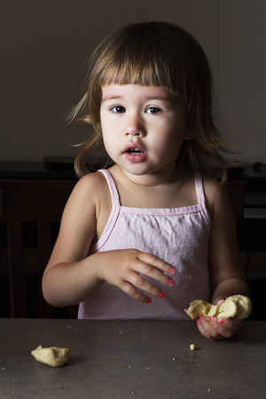 learns: Little girl learns to make dough figurines in the room Stock Photo