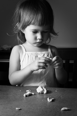 little dough: Little girl learns to make dough figurines in the room Stock Photo