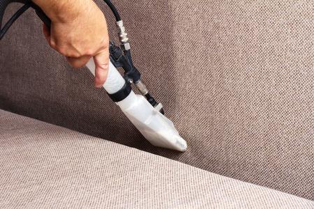 manos sucias: Limpieza profesional de la tapicería en un sofá