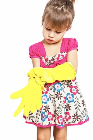 niños vistiendose: Niña en guantes de goma en el fondo blanco Foto de archivo