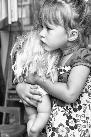 kindergartner: Cheerful little girl with a doll