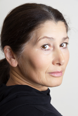 Portrait of middle age Asian woman stares seriously
