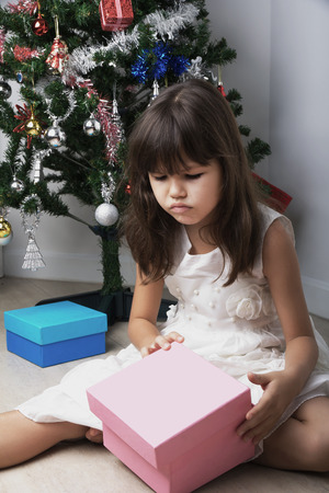 child laughing: Little girl opening christmas present