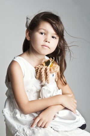 cuddles: Adorable little girl cuddles and plays with her doll