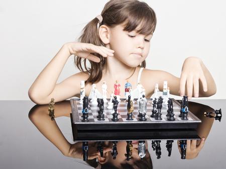 jugando ajedrez: Ni�a adorable que juega a ajedrez Foto de archivo