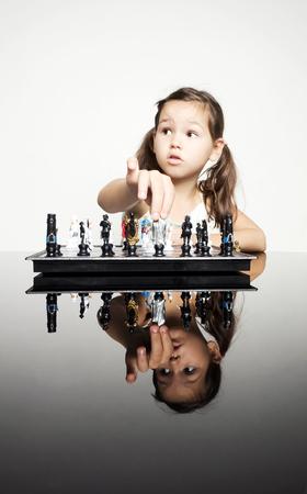 jugando ajedrez: Niña adorable que juega a ajedrez Foto de archivo