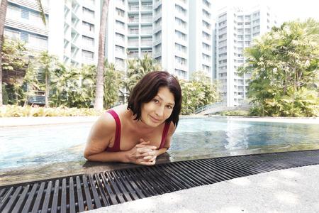 mujer ba�andose: Retrato de mujer de ba�o en la piscina Foto de archivo
