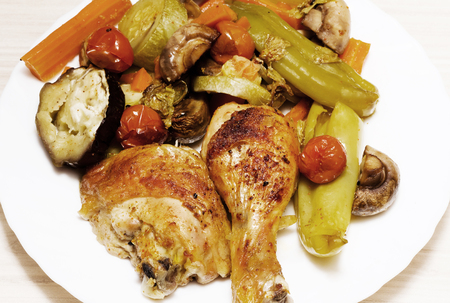 broiling: Chicken and vegetables baked in oven, studio shot
