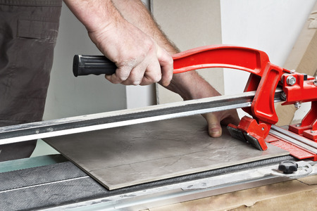 modernize: Renovation - Man construction worker laying floor tile