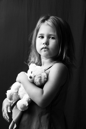 cuddles: Adorable little girl cuddles and plays with her Teddy bear